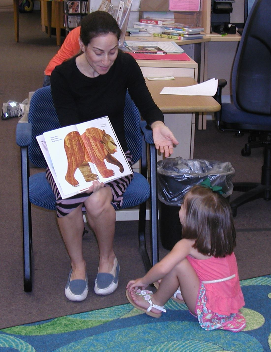 Librarian reading to child.